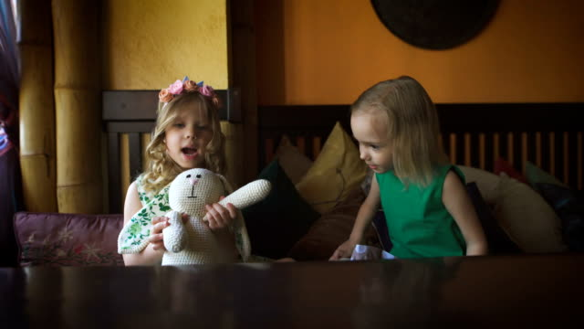 Two cute little girls are playing in a cafe video