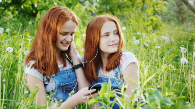 Two cute twin sisters relax on the nature, use a smartphone, listen to music on headphones video