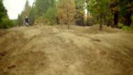 Two cyclist ride over rough dirt terrain video