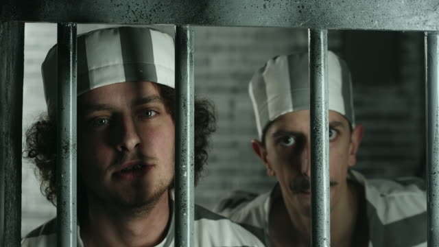 Two dangerous prisoners looking through the prison bars video