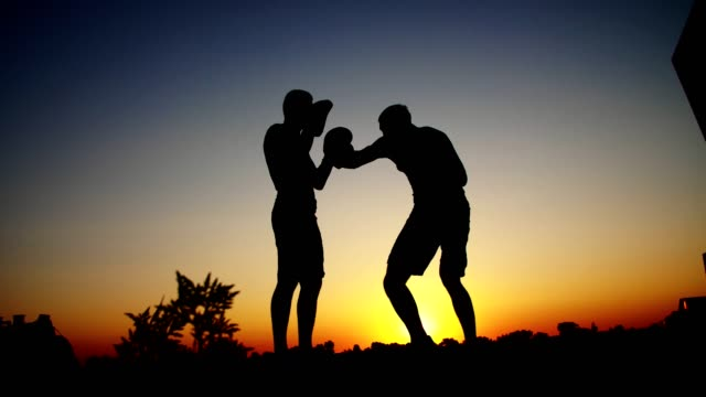 Two dark male figures, at sunrise, against the light, boxing, fighting in sparring, training in a pair of techniques of strikes. On sandy beach, in cargo port, near water, in summer video