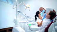 Two dentists making a patient examination video