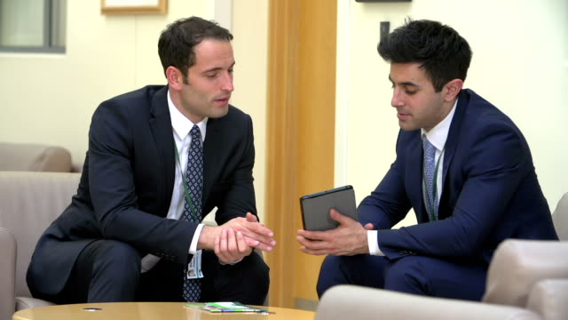 Two Doctors Discussing Patient Notes On Digital Tablet video