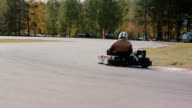 Two drivers on a go-kart track pass by the camera. Go-kart race video