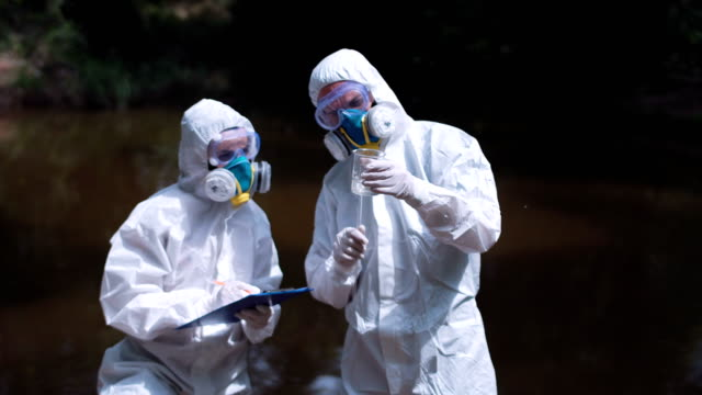 Two ecological workers in biohazard discuss water video