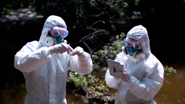 Two ecological workers in biohazard suits sampling water video