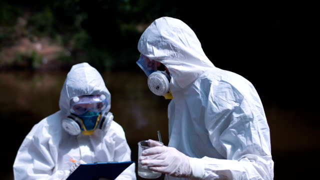 Two ecological workers in biohazard suits testing water video