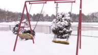 Two empty swing chairs oscillating in a park with winter scenery video