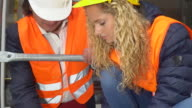 Two engineers, a man and a young blonde girl, examining plans among scaffolding video