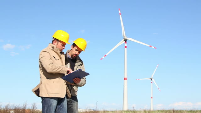 HD: Two Engineers at Work with Wind Turbine on Background video