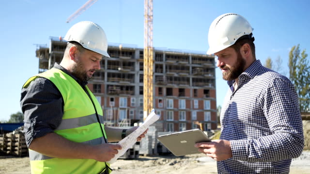 Two engineers consulting  work progress at construction. video