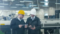 Two engineers discuss a blueprint while checking information on a tablet computer in a factory. video