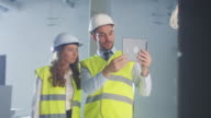 Two Engineers in Hard Hat are using Tablet Computer for Augmented Reality. video