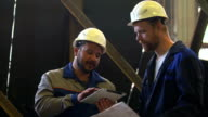 Two engineers in hardhats discussing in front of welding process video