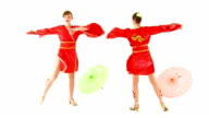 Two European girls, dancing among the umbrellas in Chinese costumes. video
