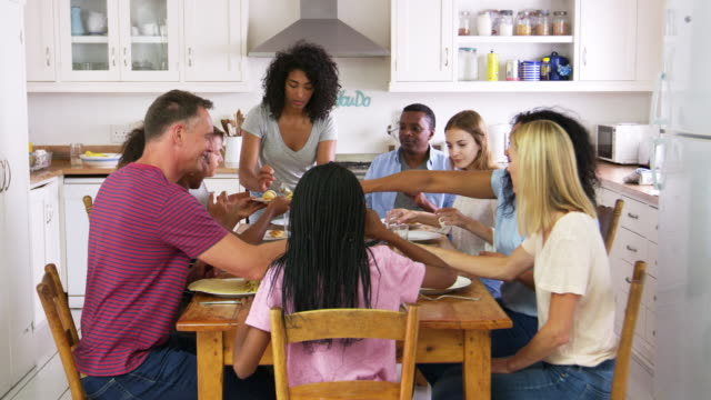 Two Families With Teenage Children Eating Meal In Kitchen video