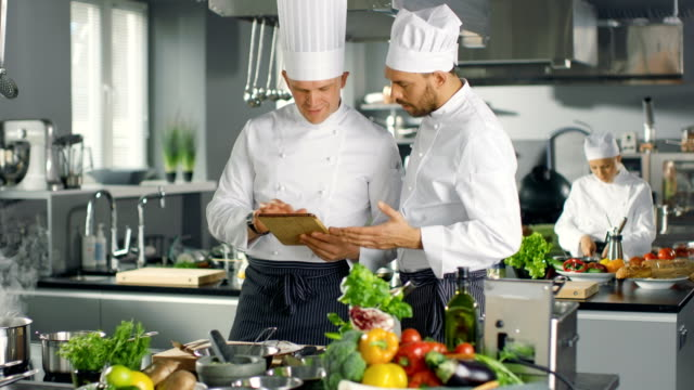 Two Famous Chefs Discuss Their Video Blog while Using Tablet Computer. They Work in Big Restaurant Stainless Steel Professional Kitchen. video
