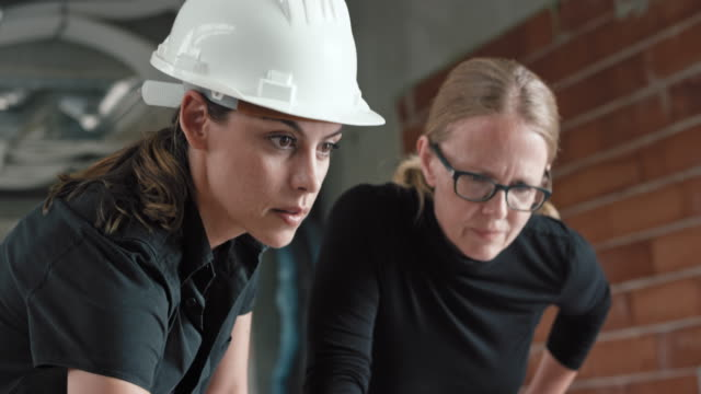 Two female architects discussing the plans on the table at the construction site and using a laptop video