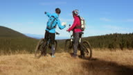 Two female bikers discussing the trail on the map video