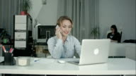 Two female coworkers working together answering phone calls in the office video