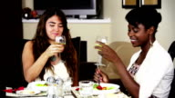 Two female friends enjoying lunch and toasting. video