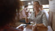 Two female friends having a drink at a table in a bar video