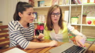 Two female friends in bookstore looking at laptop. video