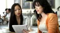 Two Female Friends In Coffee Shop Looking At Digital Tablet video