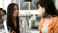 Two Female Friends In Coffee Shop Looking At Mobile Phone video