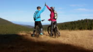 SLO MO Two female friends on bikes doing high five video