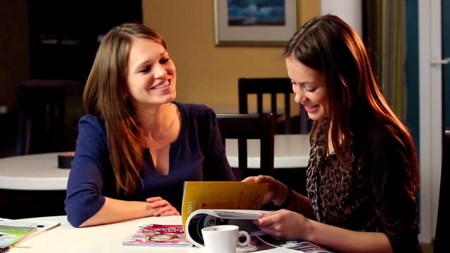 Two female friends read magazine laughing, girls company smile video