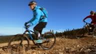 SLO MO Two female friends riding bikes on mountain trail video