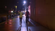 TS Two female friends running on rainy night in city video