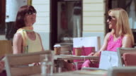 TU Two female friends talking over coffee in the sun video