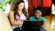 Two female friends with laptop video