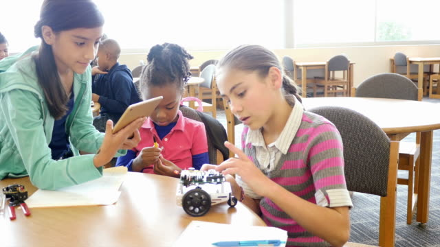 Two female Hispanic elementary school students work with younger African American female student on a robot at STEM school video