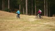 Two female mountain bikers riding through mountain meadow video