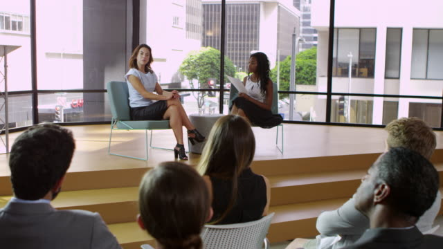 Two female speakers talking to audience at business seminar, shot on R3D video