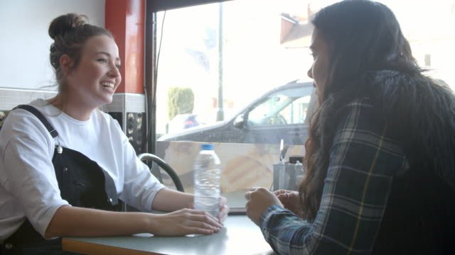 Two Female Students Hanging Out In Cafe Together video