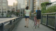 Two female young adults talking and walking across bridge with bike video