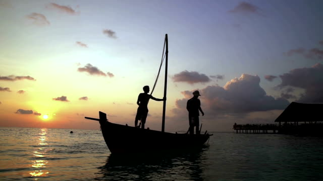 Two fishermen scooped water out of an old wooden boat at the end of a hard day at sunset in the Indian Ocean. Slow motion. video