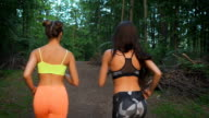 Two fitness girls running through the woods. They practice sport life style. For the health and tone video
