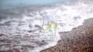 Two forgotten glasses with champagne on the surf. video