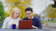Two friend multiethnicity - Korean man and a Caucasian woman working together or watching a video on a laptop. Smile, laugh, have a good time video