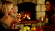 Two friend sitting near fireplace and laughing video