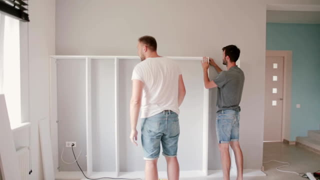 Two friends assembling the shelf, do the repairs. Man helping to his friend moving to new house video