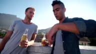 Two friends drinking and talking on the rooftop at sunset video