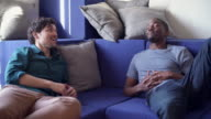 Two friends, Hispanic and Black young men, have conversation in the living room video