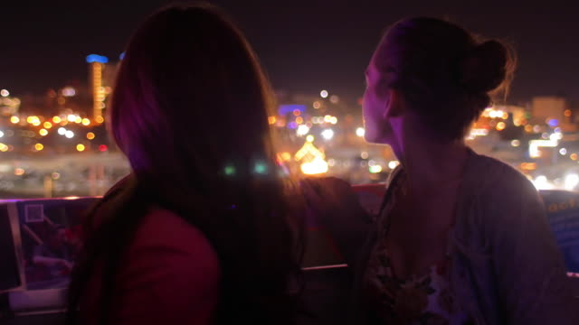 Two friends on a ferris wheel at night video