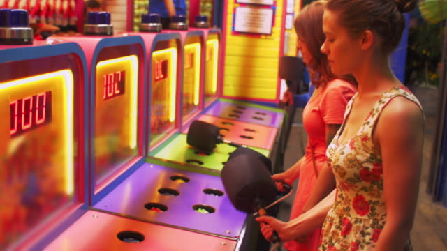 Two friends play a carnival arcade game video